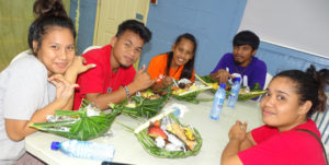 """Students enjoy the local food in their """"enra"""" (woven food baskets) as part of their Marshallese Studies course. Photo: Kelly Lorennij."""