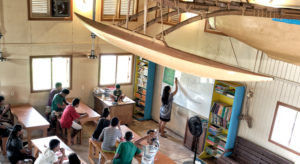 A traditional canoe built by the Waan Aelon in Majel (Canoes of the Marshall Islands) team soars above the WAM classroom, where a group of 25 trainees is engaged in the latest six-month vocational and life skills training.