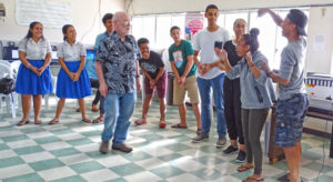 A rehearsal session for The Music Man gets the actors involved in learning how to express themselves for the musical. Professor Andrew Garrod is in the center, with Dartmouth Students Tyler Malbreaux and Summer Cody at right with local students. Photo: Hilary Hosia.